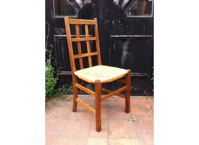 Heals. An Arts & Crafts oak rush seat lattice back side chair.