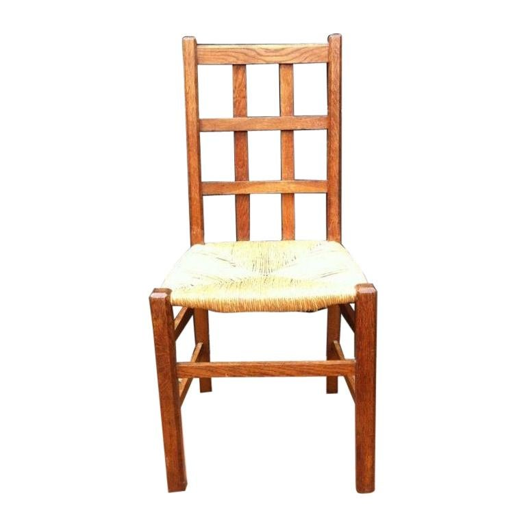 Heals, an Arts & Crafts Oak Rush Seat Lattice Back Side Chair For Sale