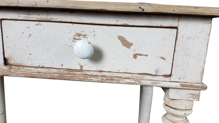 A nice side table by Heals & Sons of London, it has been carefully taken back to its original painted finish. The table sits on four white porcelain castors and has the two original porcelain handles although one is chipped. The top has been