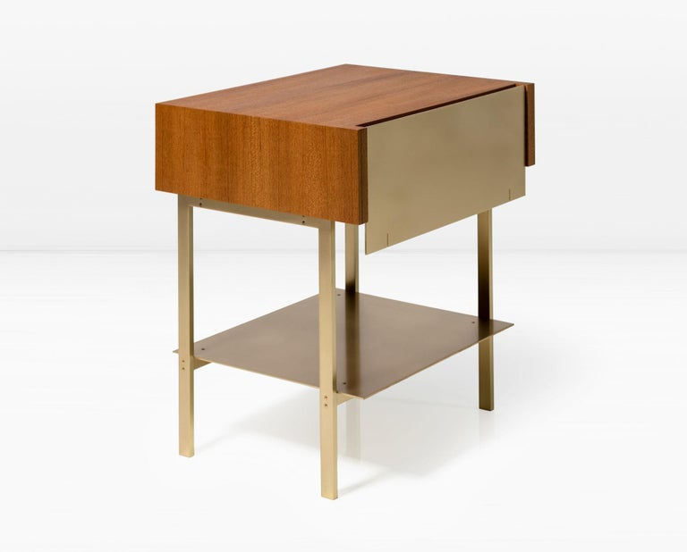The Hearns end table combines planes of solid brass in combination with a wood veneered form in a juxtaposition of two and three dimensional shapes. The drawer is accessed via a recess in the wood to eliminate the need for a pull. Premium version