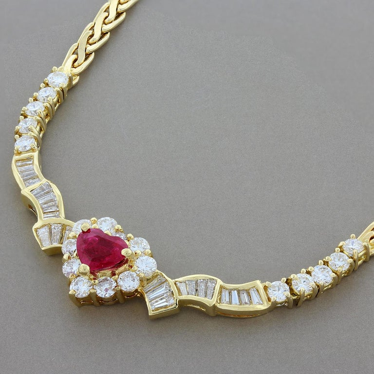 This beautifully designed necklace features a 0.91 carat heart shaped ruby accented by 2.37 carats of VS quality round and baguette cut diamonds. The 18K yellow gold setting has a quilted chain with a lobster claw clasp for a secure