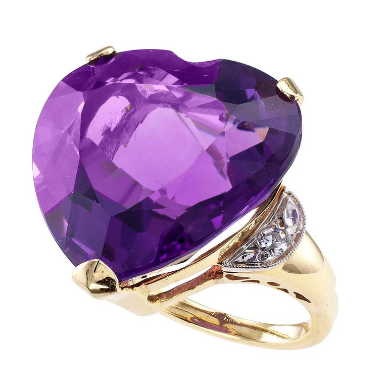 Heart shaped amethyst diamond and gold cocktail ring circa 1960. Showcasing a heart-shaped amethyst weighing approximately 23.00 carats, between halfmoon-shaped shoulders set with a pair of single-cut diamonds totaling approximately 0.06 carat,