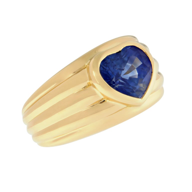 This ring features a bezel set heart-shaped blue sapphire center with ribbed grooves on the band adding to the charm of this 18k yellow gold band ring.  Perfect gift for Valentines Day, Mothers Day, Graduation, or just about any other occasion. Ring