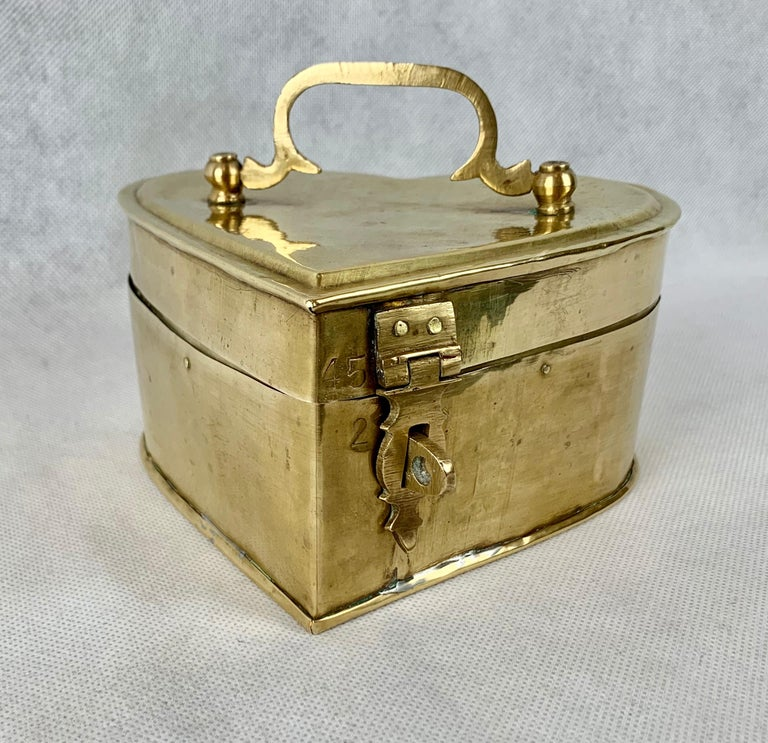 Interesting heart shaped hinged box in brass with a dfold down handle.  What makes it interesting is that it is obviously handcrafted. Measures: Height-3 1/2