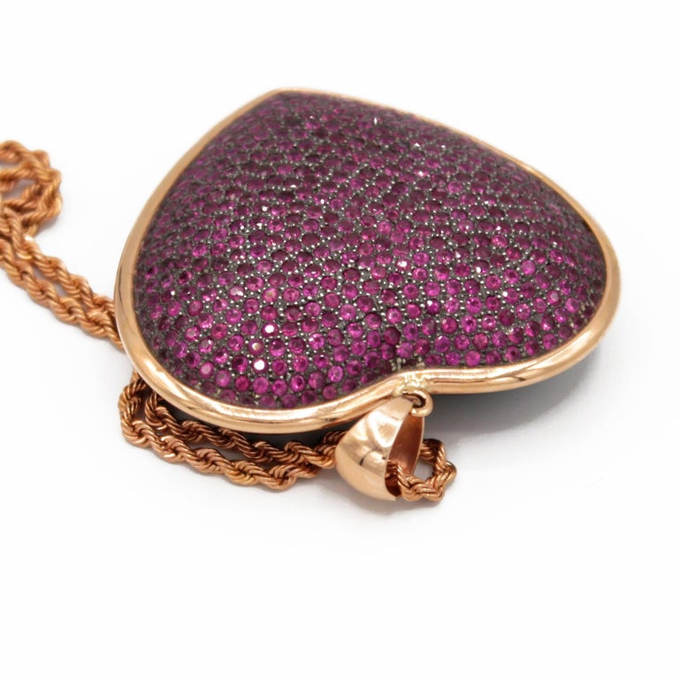Pendant necklace realized in : Rubies pave on silver setting, Bakelite back and 18kt pink gold.  Heart size : 45 x 42 mm  Rubies ct. 9,3 on silver setting and bakelite back part Gold g. 6 18kt pink gold chain g. 2,9. Lenght 50 cm.  Total weight