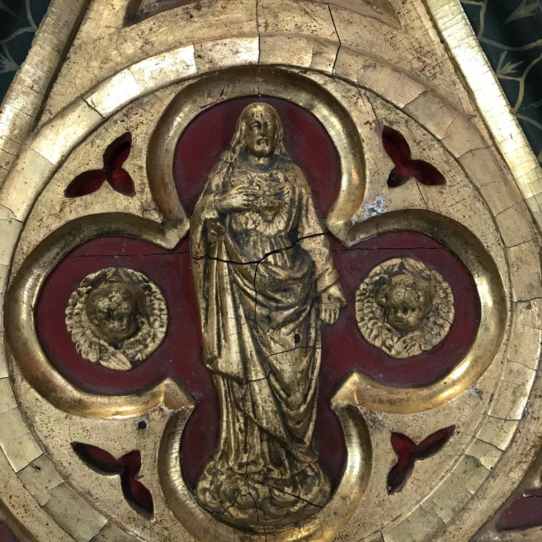 """An incredible eye catching piece of wall art mined from a 19th century French church. The wall sculpture is a Gothic shape having carved giltwood and beautifully painted bas relief art at the top of a saint with cherubs. """"Confrerie des Dames de"""