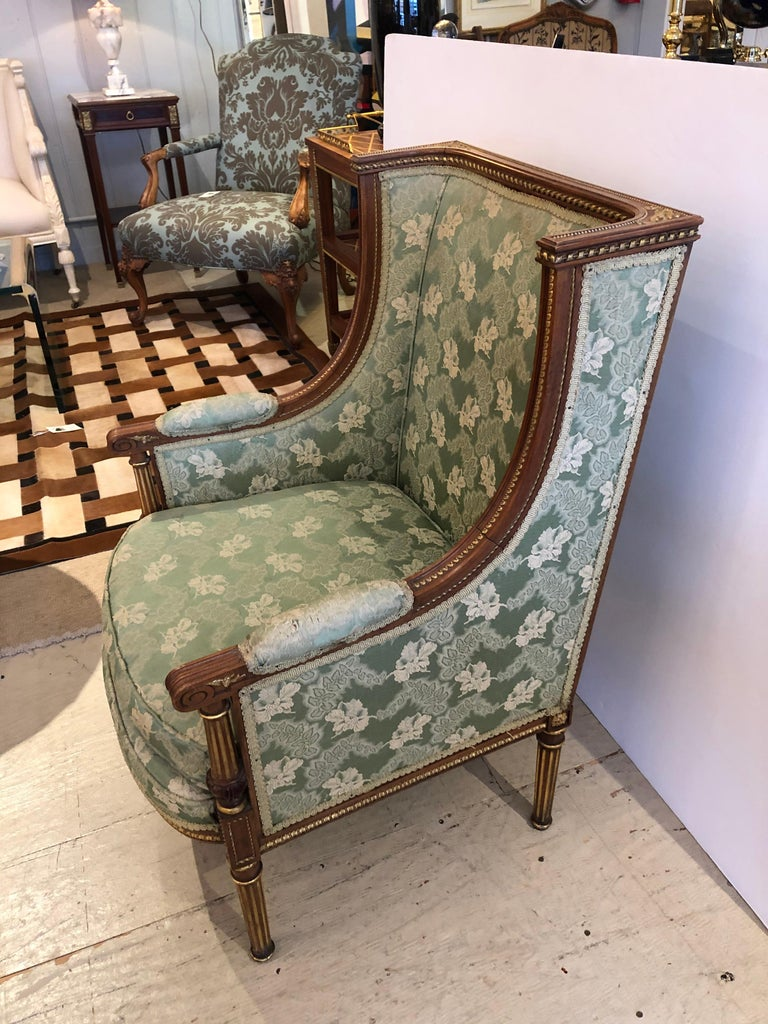 An utterly sublime French Louis XVI style bergère sized for a princess having gilded carved walnut frame with magnificent detailing, reeded legs, and original green satin brocade. Upholstery shows some wear especially on the arm pads. Measures: Arm