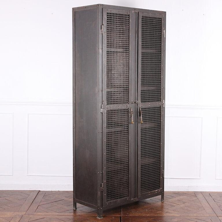 Unusual heavy (about 350lbs) steel cabinet with pierced mesh doors which open to four fixed welded shelves. The corners and doors of the cabinet are reinforced with riveted thick gauge steel plate. Handsome turned drop-pull handles; simple latches