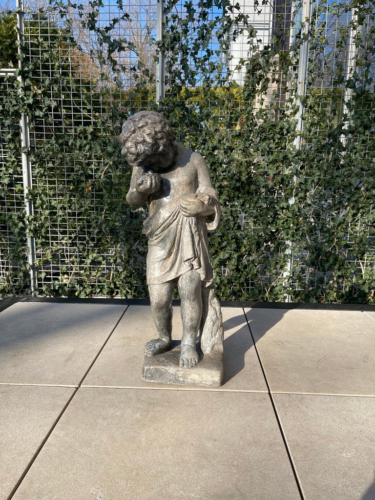 Lead putto statue depicting an Italian curly haired young boy, with animal skin around his waist and draped over his forearm. He gazes closely at a nest with two baby birds that he holds gently in his right hand. He stands at 24.75