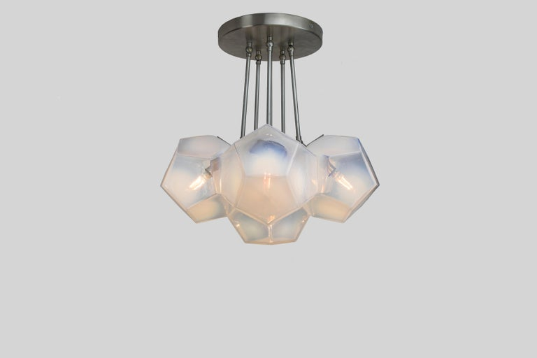 The Hedron Series Chandelier in Opaline is comprised of six moldblown glass dodecahedrons arranged in a calculated cluster. Paired with satin nickel hardware and ceiling canopy, the opaline colored fixtures create a faceted array of luminance. Each