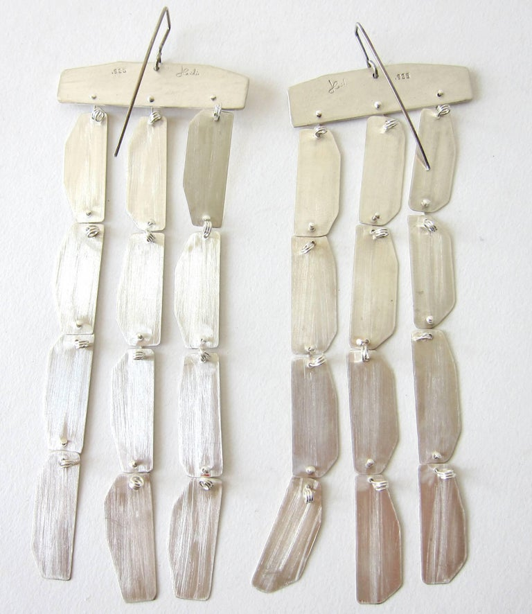 Handmade, jointed brushed sterling silver earrings created by Heidi Abrahamson of Phoenix, Arizona.  Earrings measure 5