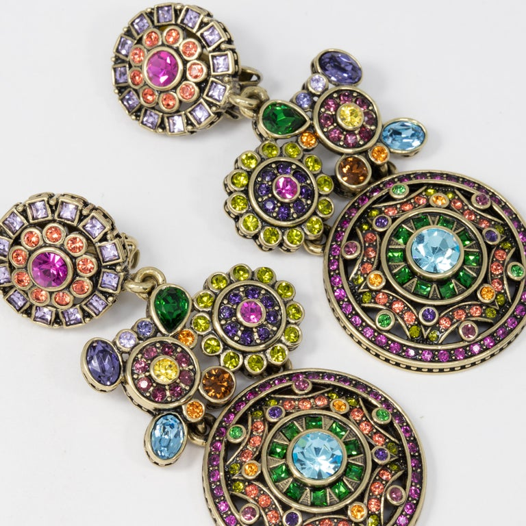 Heidi Daus ornate dangling clip on earrings. Each features large round flower and abstract motifs adorned with colorful crystals.  Hallmarks: Heidi Daus, China