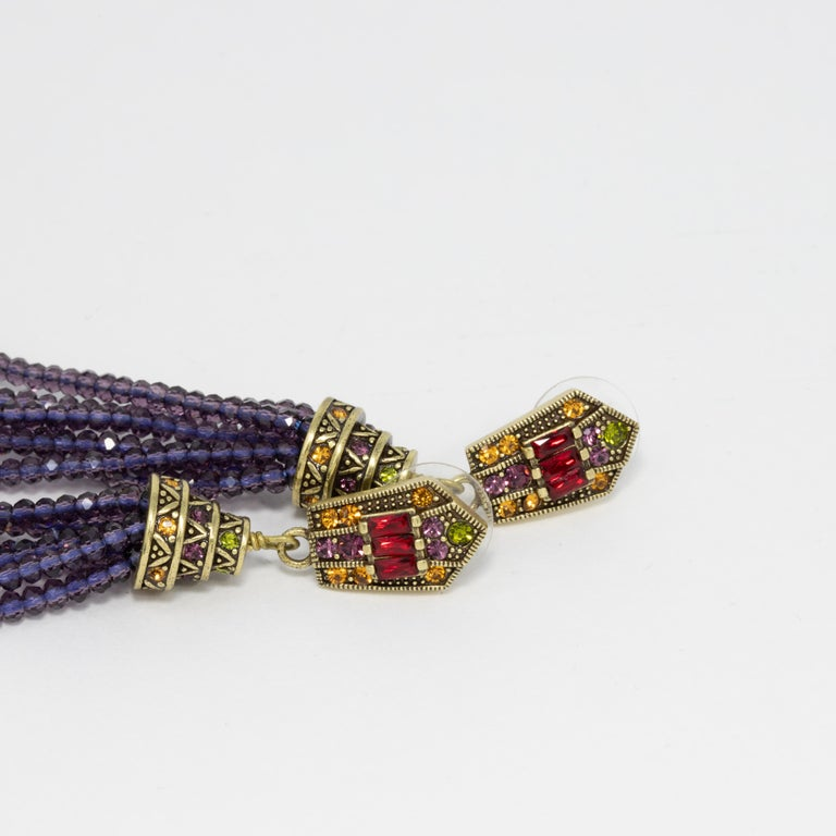 Embellished dangling post-back earrings by Heidi Daus. Feature ruby red and citrine crystal tops with dangling purple and green crystal tassels.  Hallmarks: Heidi Daus, China