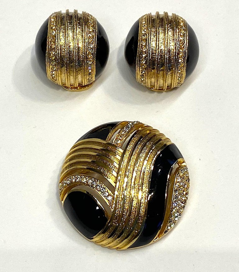 Helena Rubinstein 1980s Art Deco style gold tone dome brooch and earring set. The domed brooch has cut out stripes that follow the gold stripe design, black enamel and rhinestone accents. It is 1.63 inches in diameter and .63 of an inch high. The