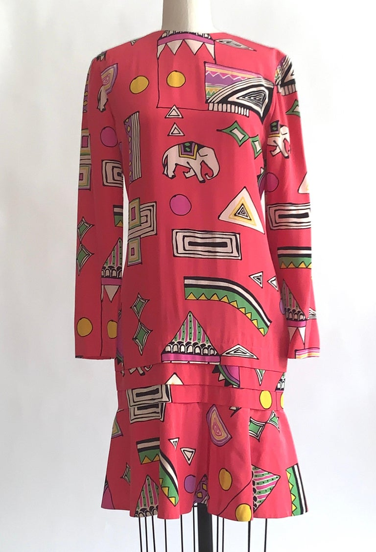 Helga bright pink vintage dress with vibrant multi color abstract circus print throughout featuring elephants and circus tents. Flounced hem with pleat detail above. Long sleeve. Back zip.   No content label, feels like silk, but could be a blend.