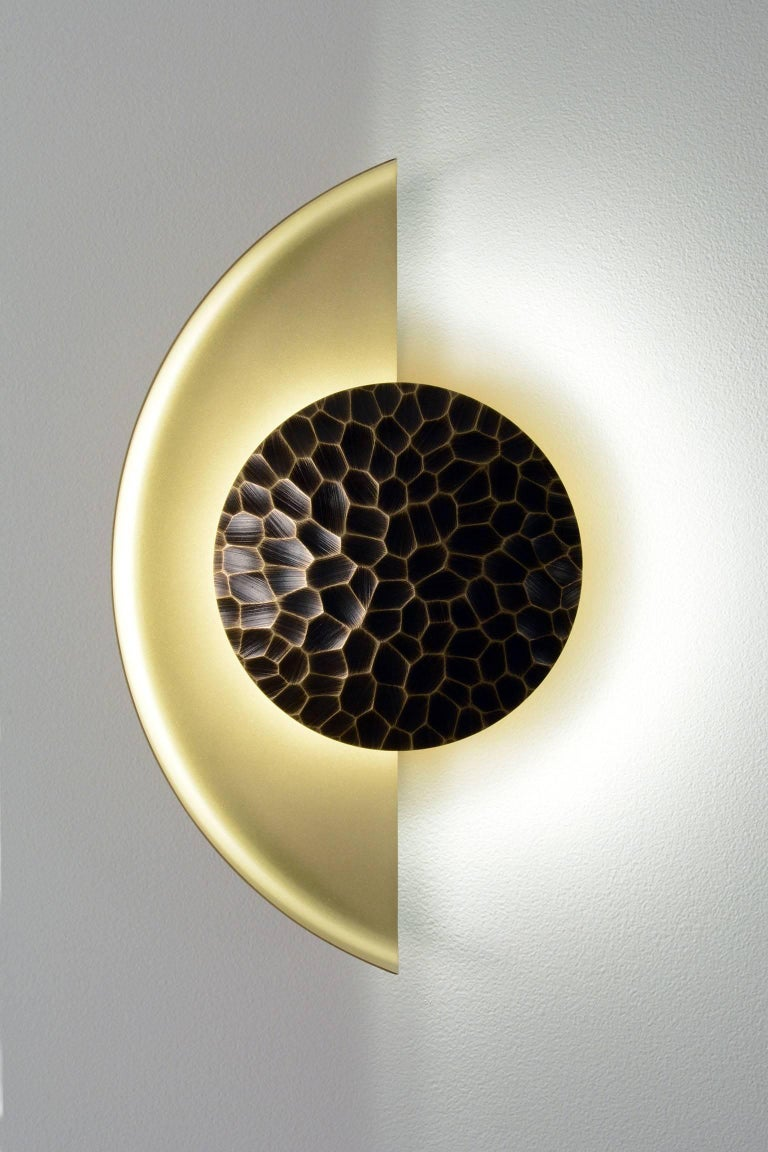 The Helix sconce is a dimmable LED wall sconce featuring a crescent shaped dome and etched bronze shield. The shape of this sconce creates a stunning array of shadows and reflections. The example shown above features a sandblasted brass body and