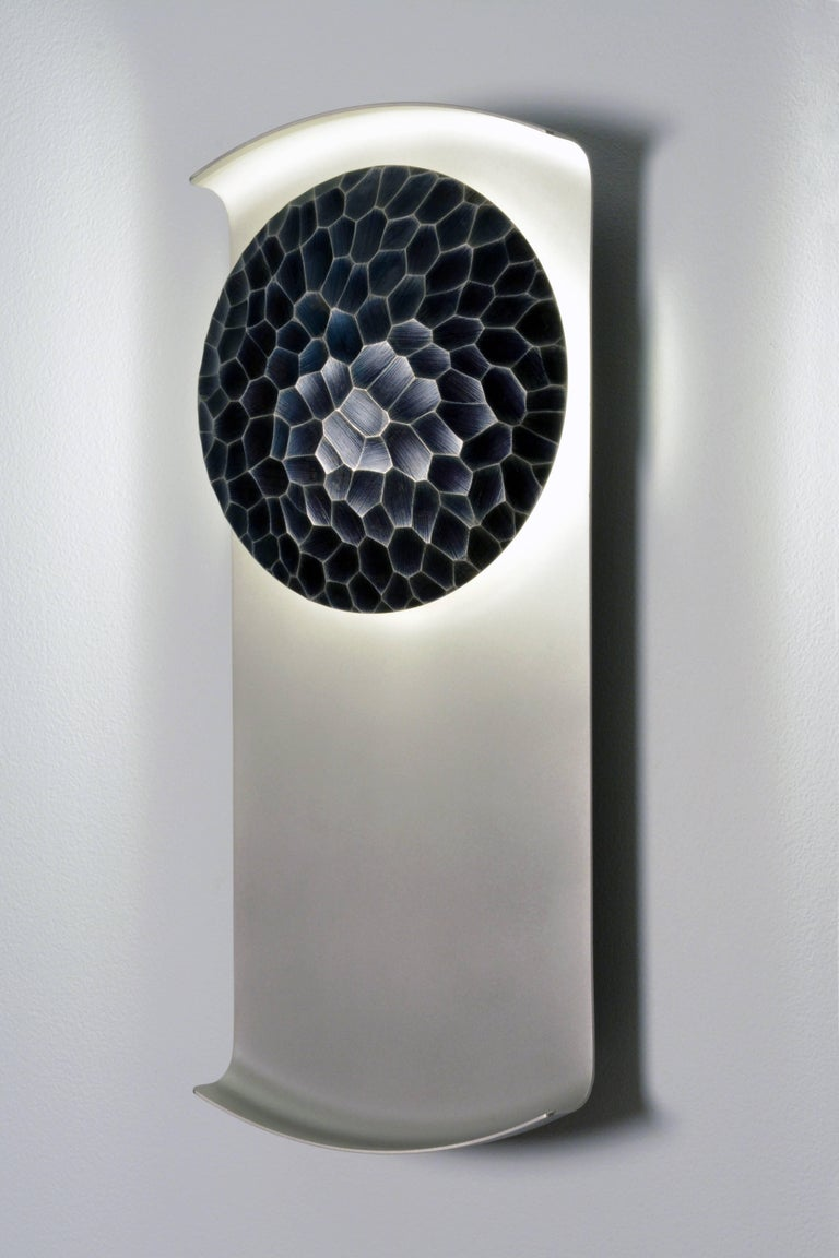 The Helix sconce is a dimmable LED wall sconce featuring a linear body and etched bronze shield. The shape of this sconce creates a stunning array of shadows and reflections. The example shown above features a sandblasted nickel body and blackened