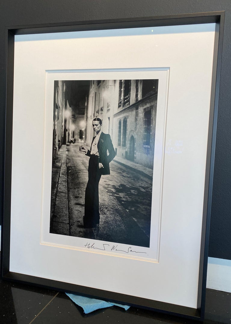 HELMUT NEWTON (1920–2004) Yves St. Laurent, Rue Aubriot, French Vogue, Paris, 1975 gelatin silver print Signed by artist on recto in margin, date inscription and estate stamp on verso  image: 22 5/8 x 14 3/4 in. (57.4 x 37.4 cm.) sheet: 23 3/4 x 19