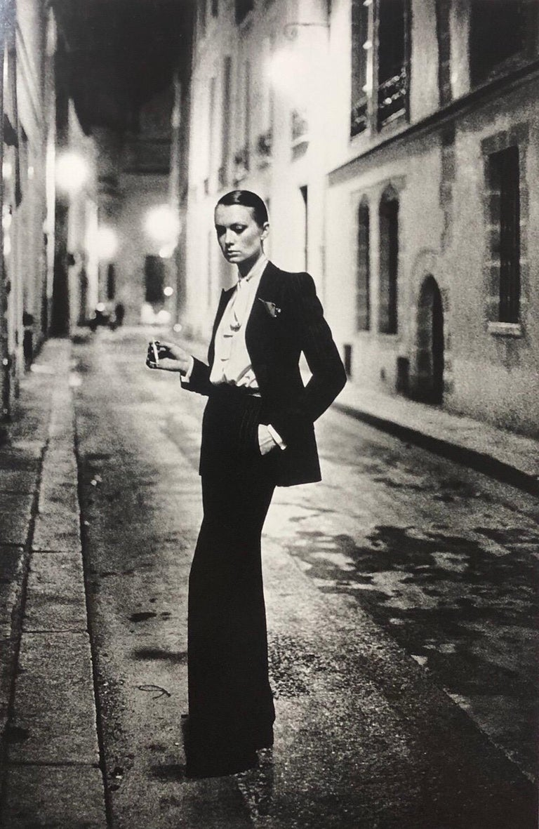 """Original early 1980's silver gelatin print title """"Rue Aubriot"""" featuring actress Vibeke Knudsen alone in a lamp lit Parisian street. The image has become one of Helmut Newton's most popular and widely collected.  Styled in a deliberately androgynous"""