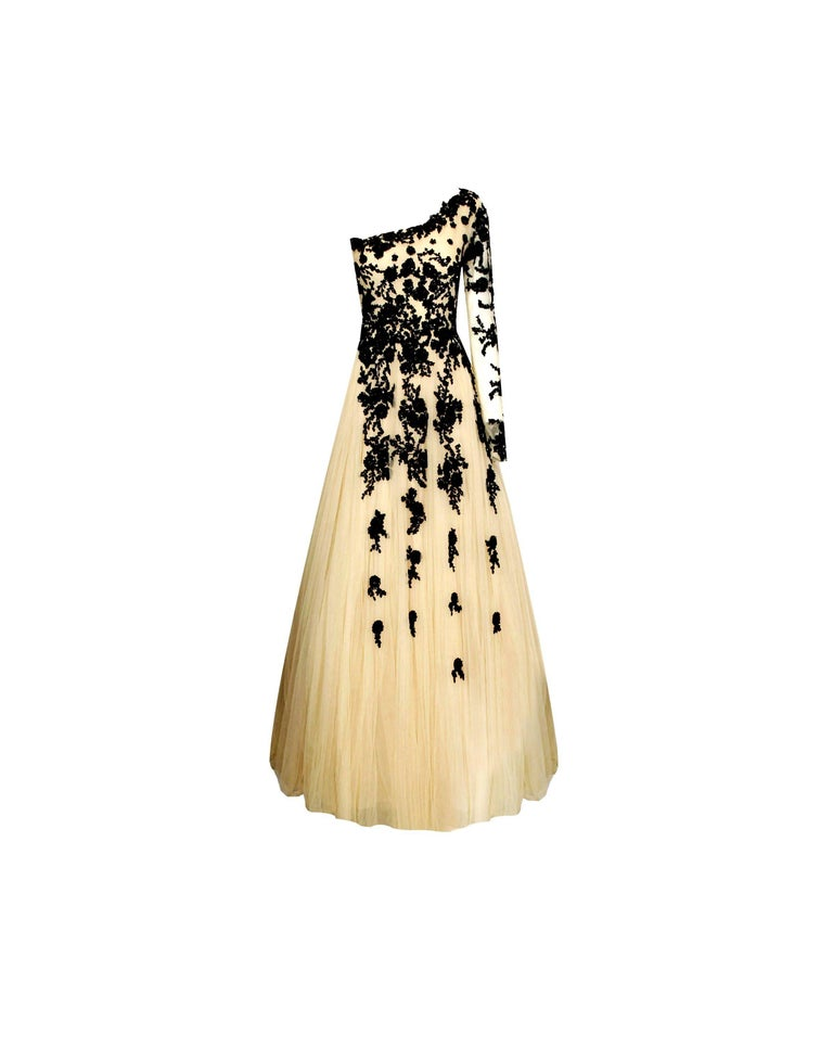 This gown is a very special piece and a head-turner designed by Hema Kaul Live your own modern fairytale Light nude color Asymmetric design with open shoulder Full-length Finest tulle fabric in several layers for a full-bodied look Gorgeous black