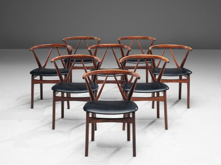 Henning Kjaernulf for Bruno Hansen, set of eight dining chairs model 255, rosewood and faux-leather, Denmark, 1950s. 