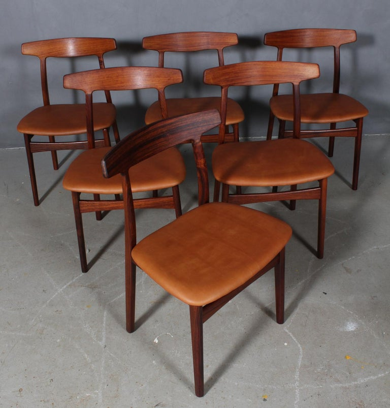 Henning Kjærnulf six dining chairs, upholstered with tan aniline leather.  Frame of solid rosewood.  Made by Bruno Knudsen.