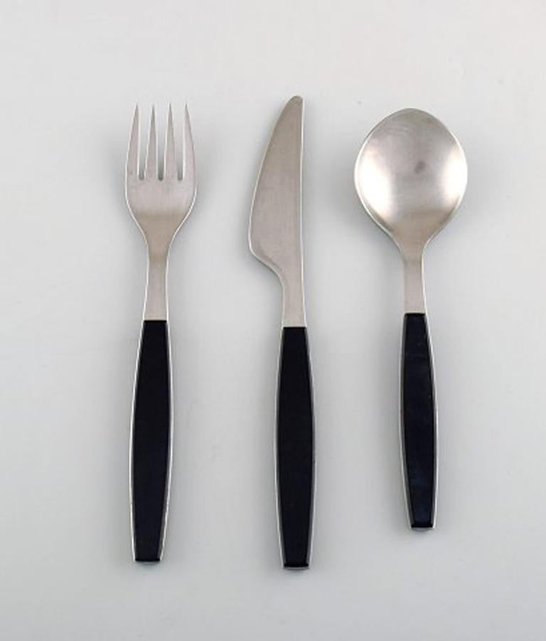 Henning Koppel. Complete four-person dinner service. Strata cutlery stainless steel and black plastic. Manufactured by Georg Jensen. Comprising: Four dinner knives, four dinner forks, four table spoons. In very good condition. Danish design