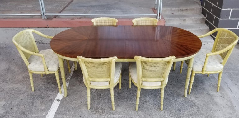 A fine quality seven piece dining set by Henredon Furniture. Faux bamboo design with original celadon or spring green painted finish. Beautiful fanned and book-matched walnut table top with two 20