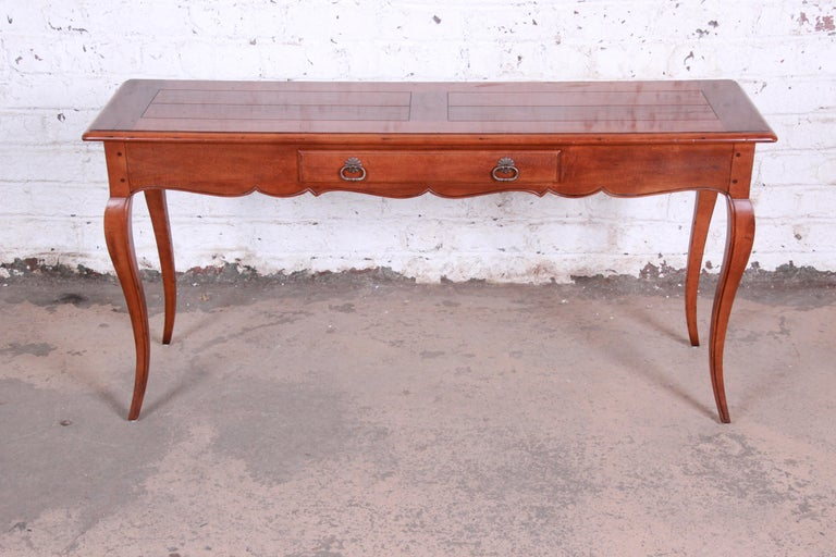 A gorgeous French Provincial Louis XV style console or sofa table by Henredon. The table features solid cherry wood construction with beautiful wood grain and tall cabriole legs. It has a single drawer for storage, and the original Henredon label is