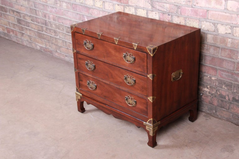 An exceptional midcentury Hollywood Regency chinoiserie bachelor chest or bedside table  By Henredon  USA, 1970s  Book-matched mahogany, with Asian-inspired etched brass hardware and accents.  Measures: 26.5