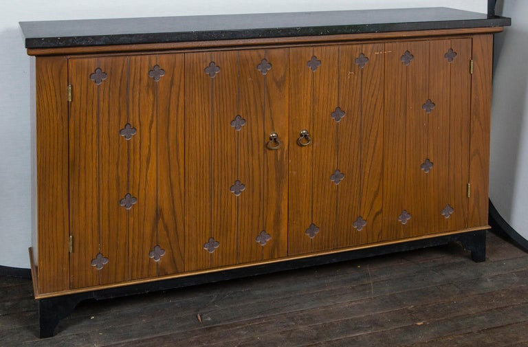 Henredon wood console/cabinet with bifold doors, black marble top. The wood doors are decorated with 24 incised quatrefoils. There is one interior shelf. Interior dimensions are 54.25 inches wide by 11 inches deep.