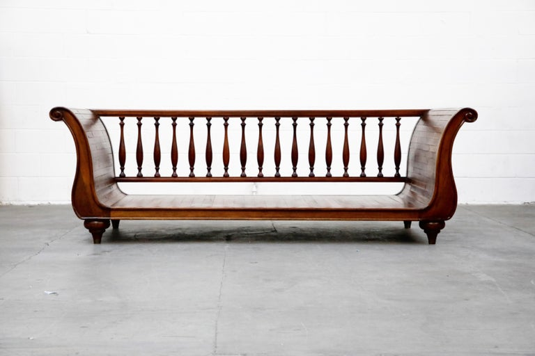 An incredible high quality wood daybed in sleigh form by Henredon. This designer piece features a spindle rail back with 17 turned wood spindles, turned wood bun legs / feet, and strips of wood planks assembled in a sleigh form with rolled arms.