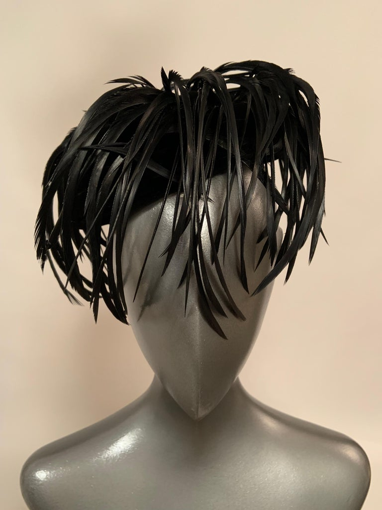 This is one of those very chic accessories that adds instant glamour to your evening look. The black velvet hat swirls from the brim to the center of the hat and then the feathers swirl over the velvet in the same circular motion, dipping over the
