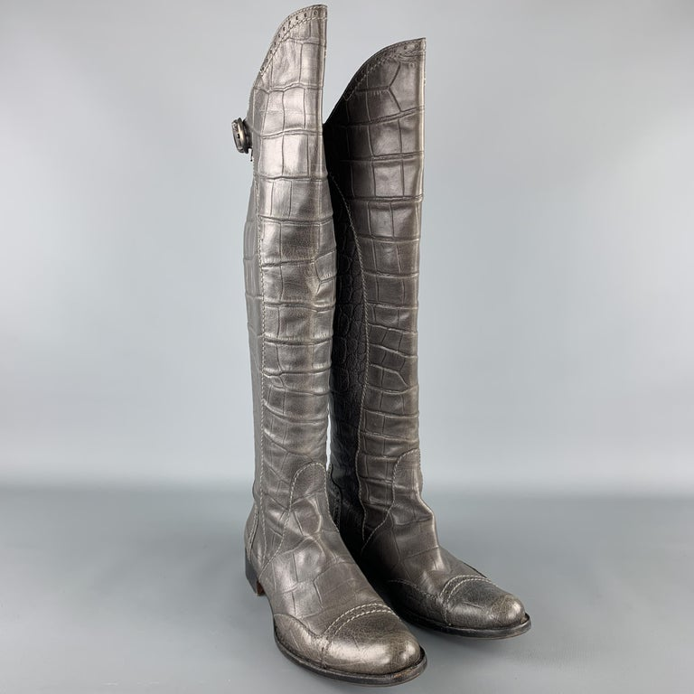 HENRY BEGUELIN boots come in grey crocodile embossed leather with a pointed cap toe, knee high shaft, and back zip closure with strap. Handmade in Italy.  Very Good Pre-Owned Condition. Marked: IT 38.5 Original Retail Price: $1,500.00  Outsole: 11 x