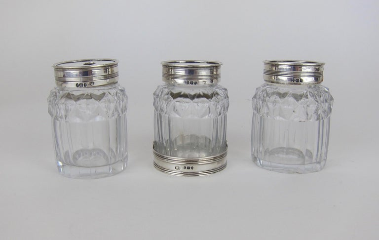 A set of three George III cut-glass bottles with sterling silver lids, made by English silversmith Henry Chawner of London and hallmarked for 1792. The antique set comes from The collection of Peggy and David Rockefeller.   The 18th century jars