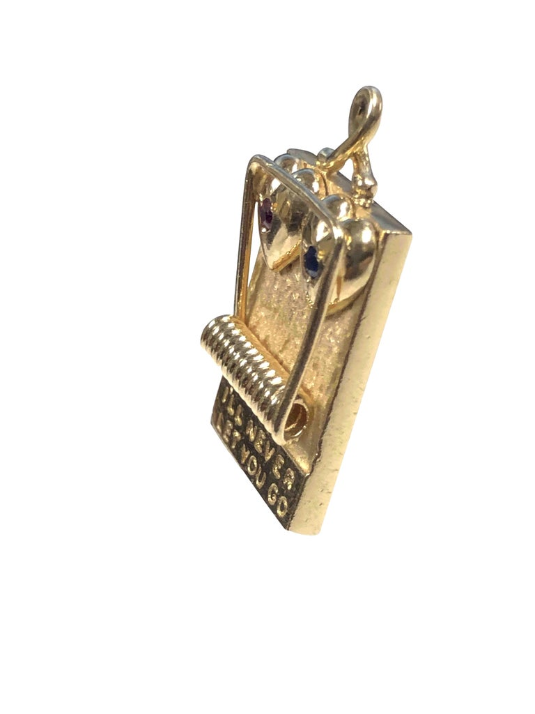 Circa 1950s Henry Dankner 14K Yellow Gold Lovers Hearts in a mouse Trap Charm, measuring 1 X 5/8 inch and weighing 7.4 Grams. Extremely well detailed and set with a Ruby and Sapphire.