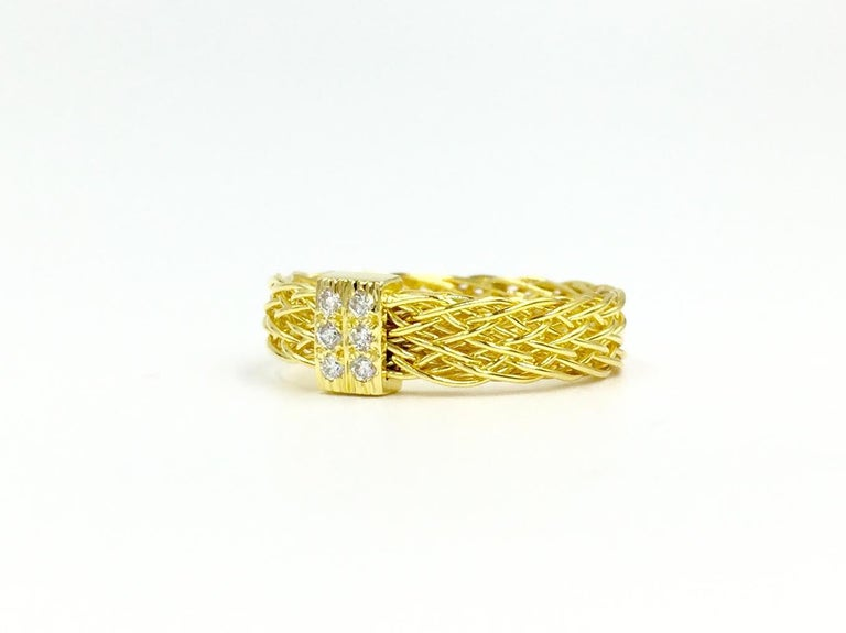 Signed Henry Dunay 18 karat yellow gold woven 4mm band style ring with 6 round diamonds at .10 carats total weight. This stylish ring is wide enough that it can be worn alone or can stack beautifully with other thin rings.  Finger size 6