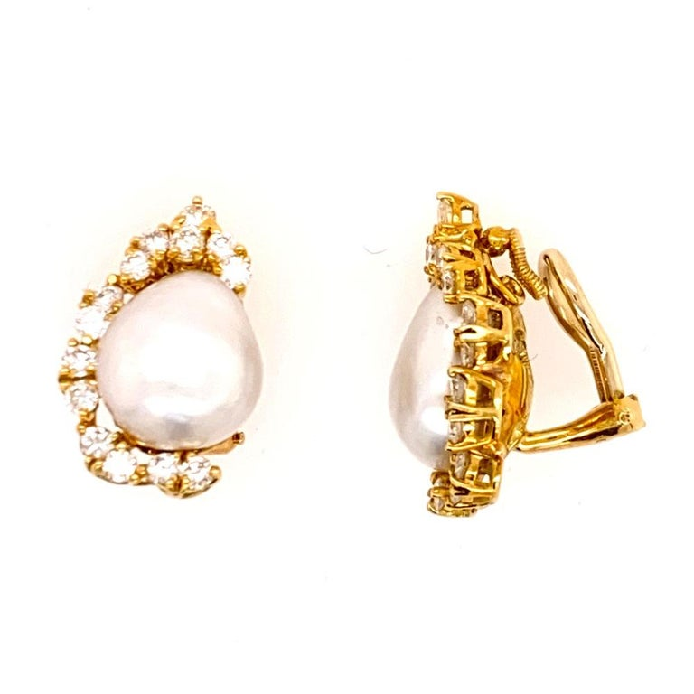 Estate baroque pearl diamond earrings by jewelry designer Henry Dunay. The earrings feature 28 round brilliant cut diamonds weighing 1.40 carats graded F-G color and VS clarity. The diamonds border the baroque pearls, and the earrings measure .5