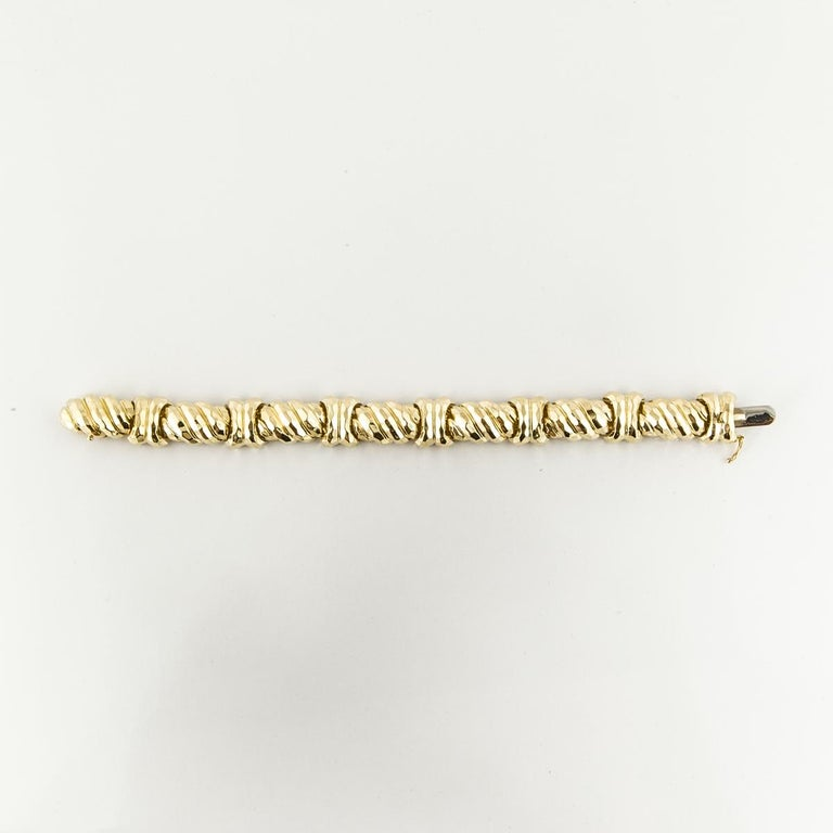 18K yellow gold bracelet by Henry Dunay.  Links are elongated, ridged and hammered.  Tongue closure with figure eight safety.  Measures 7-3/4