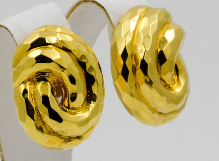 These Henry Dunay 18k yellow gold clip earrings create a polish and classic look. The earrings have a swirl pattern that consists of two intertwining loops to give a classic knotted design.
