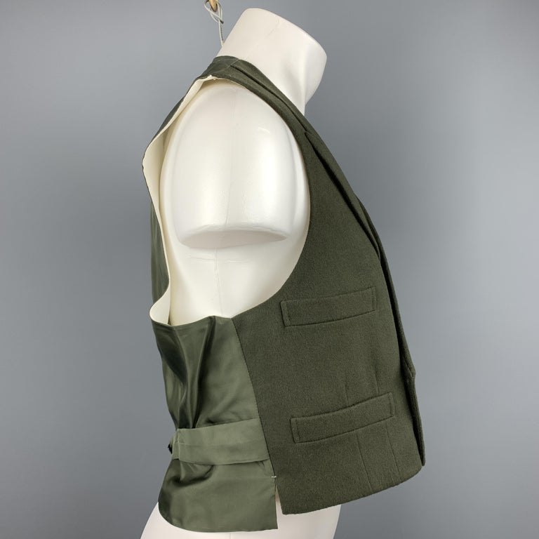 Custom Made HENRY POOLE & CO of Savile Row vest comes in a forest green wool featuring a peak lapel style, slit pockets, back belt, and a double breasted closure. Made in England.  Excellent Pre-Owned Condition. Marked: (No