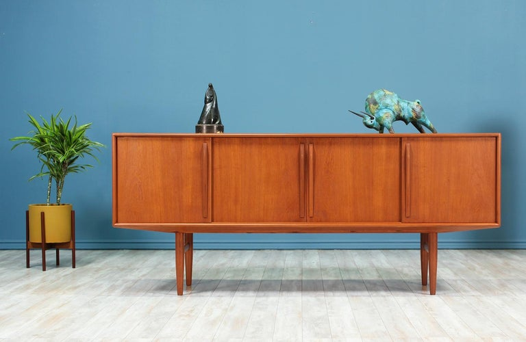 Spacious Danish Modern teak credenza designed by Kurt Østervig for Brande Møbelindustri in Denmark circa 1950's. The subtle minimalistic details on this teak credenza reflect the expert craftsmanship put into making this design. The front features