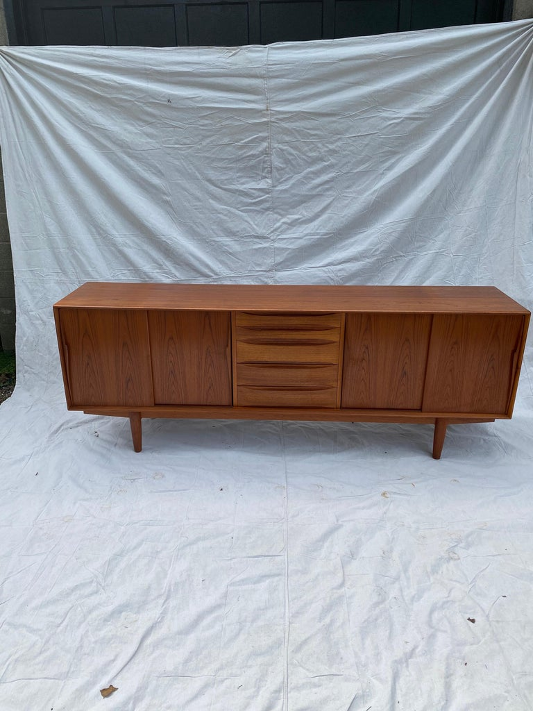 Henry Rosengren Hansen teak credenza or buffet. Beautiful design with tons of storage! 5 center drawers and 4 sliding doors open to reveal adjustable shelf's. Original finish is very nice, top shows 2 very slight shadow marks.