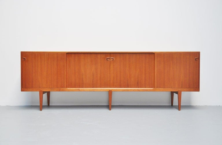 Nicely refined sideboard model 9940 designed by Henry Rosengren Hansen for Rosengren Hansen, Denmark, 1960. The sideboard has 4 sliding doors with shelves and 4 drawers behind. Very nice crafted tea handles and a nice detail is the way the legs are
