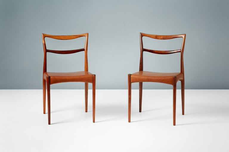 Rarely seen, sculptural dining chairs from Norwegian designer Henry W. Klein. Produced by Bramin in Denmark in exquisite Brazilian rosewood. The seats have been reupholstered in premium aniline cognac brown leather.