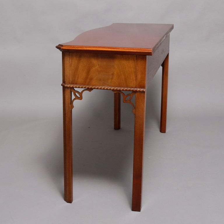 A Hepplewhite style server custom handcrafted by Councill Craftsmen offers serpentine form and flame mahogany construction with cabinet having two drawers, rope twist trimming and raised on square and tapered legs having cutout corbels, 20th