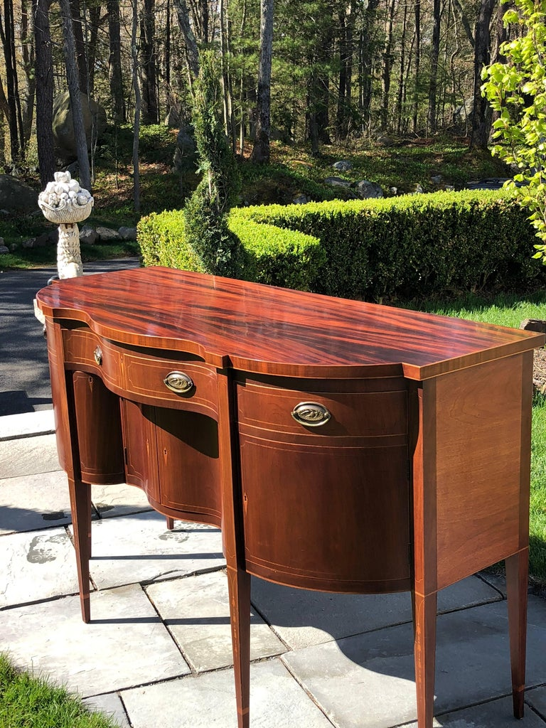 Custom serpentine front mahogany sideboard of highest quality and craftsmanship. Mortice & Tennon construction, dovetailing throughout, band inlays all around and bellflower inlays on the tapered legs. The oval brass pulls have the American Eagle in