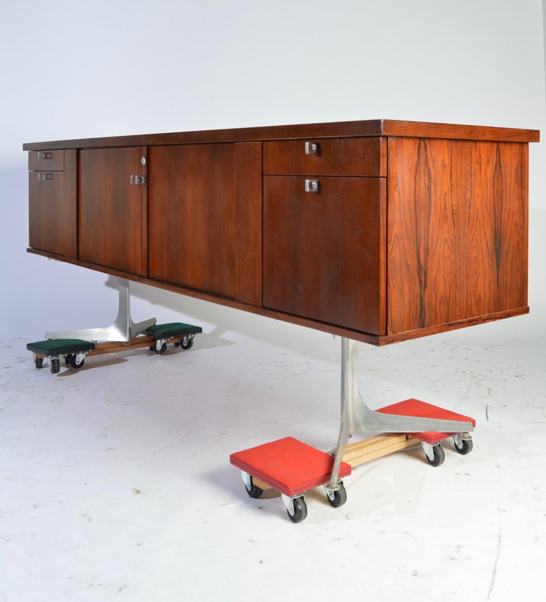 Herbert Hirche Minimalist 'Top Series' Rosewood Credenza having Tambour center doors that reveal ample case storage to the left and a wine or liquor rack to the right, which pulls out should you not need it. The left and right sides of the case
