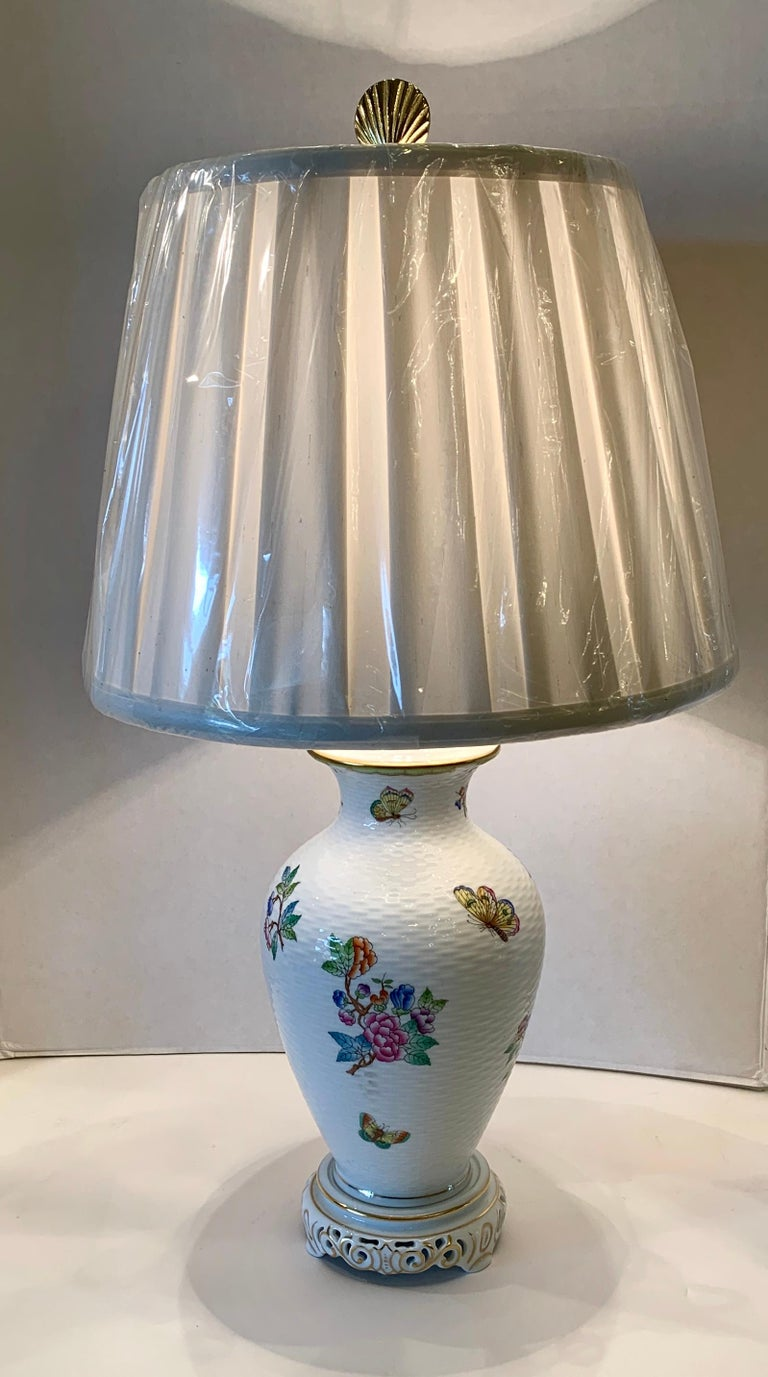 "Beautiful handmade white basketweave porcelain estate lamp from Herend in the famous ""Queen Victoria"" pattern of colorful flowers and butterflies, accented with 24 karat gold, has been hand painted by the legendary Hungarian master artisans of"