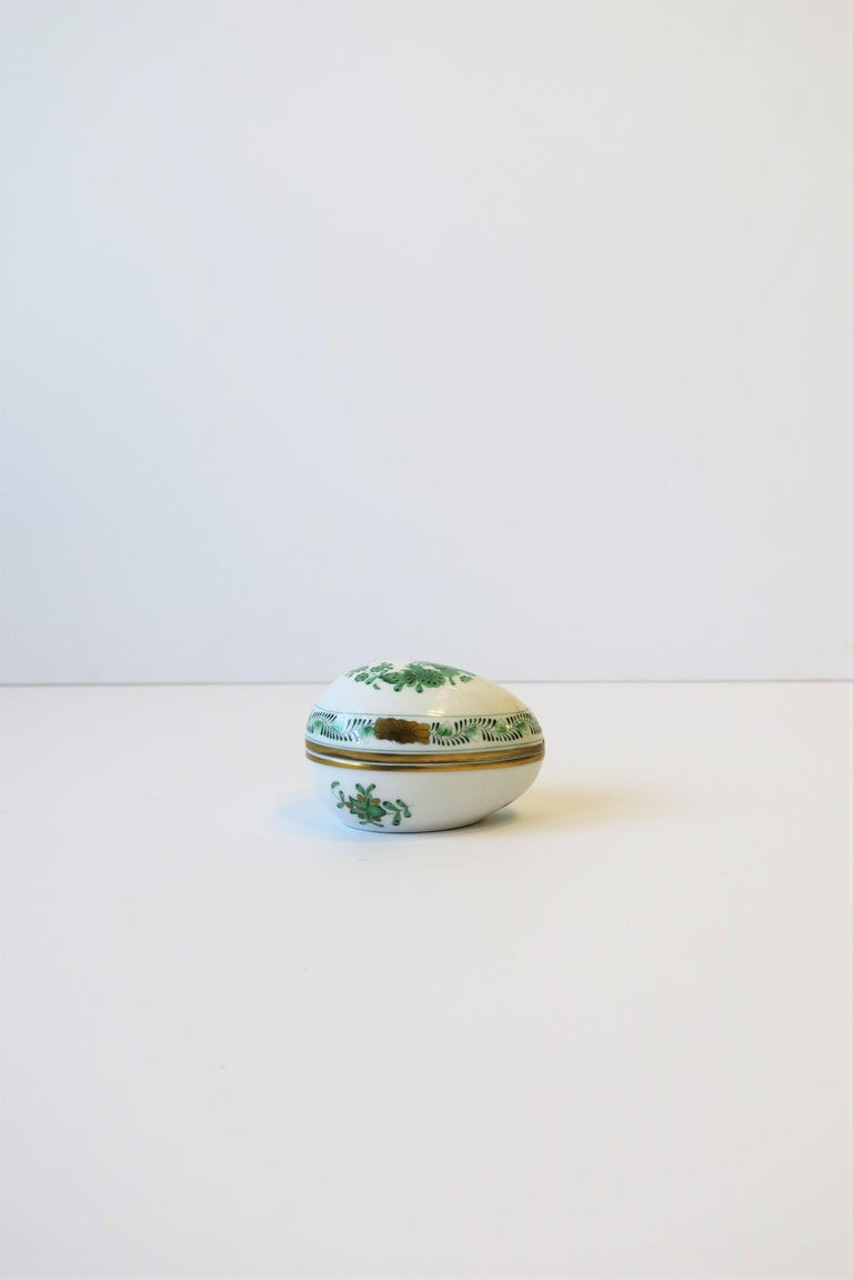 A beautiful white porcelain hand painted egg-shaped box from luxury maker HEREND, Hungary, circa 20th century. This Herend white porcelain egg-shaped box is hand painted by artist in emerald green and gold hues with a modern floral design. Box can
